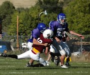 Craig Middle School defensive tackle Tyler Hildebrandt, left, sacks Soroco quarterback Nic Paxton. Hildebrandt and Bubba Ivers, right, led the Bulldog defense in the second half Tuesday, shutting down Soroco's offense on their way to the team's fourth victory in five games.