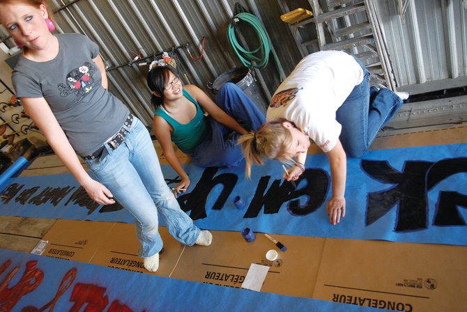 Angg Morgan, from left, Connie Le and Ashley Raymond look out as people show up to help work on the freshman float for the 2007 Moffat County High School Homecoming Parade. This year's homecoming event begins at 2 p.m. Oct. 10 at Calvary Baptist Church, 1050 Yampa Ave. Organizers are accepting applications for parade entries.