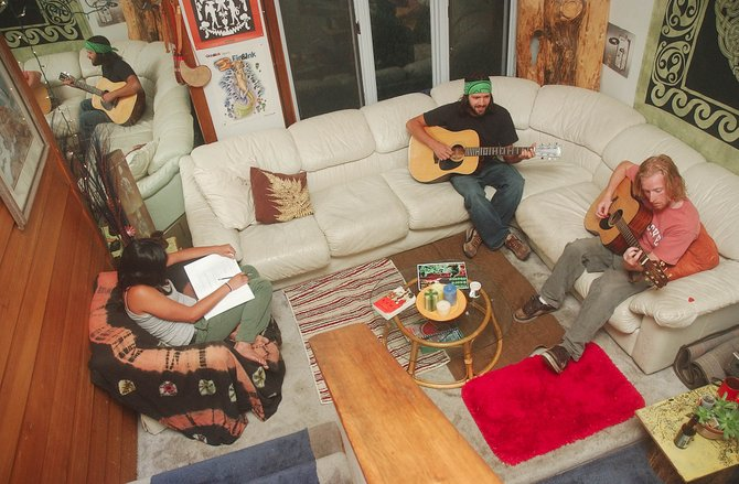 Tyler Kimball, right, and Jeff Barlow play their acoustics while Kendra Sullivan does homework.