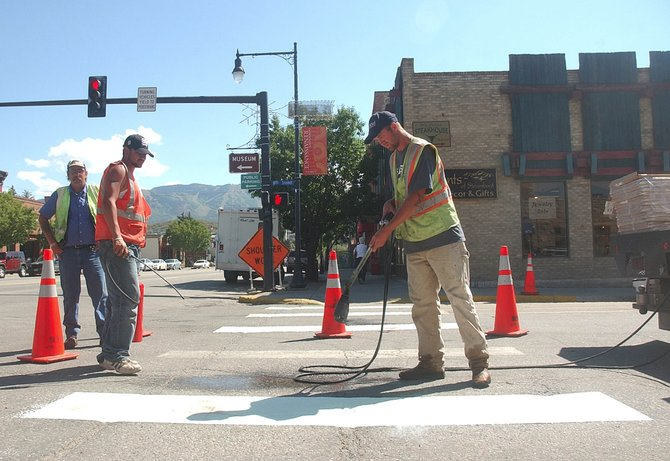 Shane Smith, right, Sal Ocano, middle, and Bob Syperreck, with Rocky Mountain Enterprises, install HotTape crosswalk striping Thursday at Eighth Street and Lincoln Avenue.