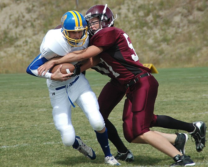 Soroco's Bobby Mason, front, and Ben Straight try to drag down Nucla's freshman quarterback, Destry Smith, on Saturday. The Rams had six sacks in the 57-22 homecoming victory.