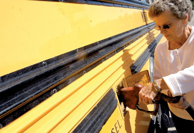 Pat Hering, a first-year driver for the Moffat County School District, fills up the tank of her bus before going out on the afternoon route.