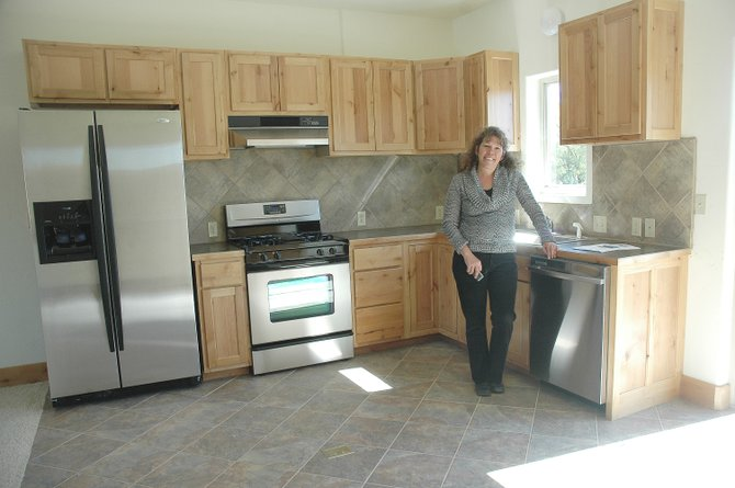 The first section of Hayden's Creek View development is nearly finished. Real estate agent Annette Hall shows off a kitchen in one of the townhomes Tuesday. Developers Louis and Stef Nijsten, who live next door to this unit, plan to rent out some of the homes.