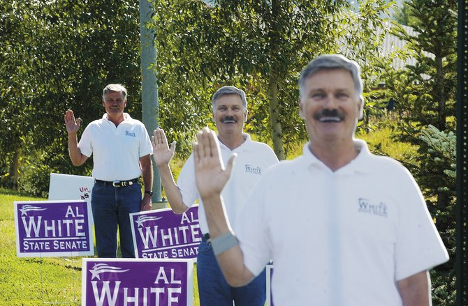 "Rep. Al White, R-Hayden, stands behind cardboard cutouts of himself to get the attention of motorists Sept. 16 along Mount Werner Road. White said he has used the technique in all of his past campaigns. ""In politics, if you make people smile, you're accomplishing something,"" he said. White is running for the state Senate against Steamboat Springs Democrat Ken Brenner."