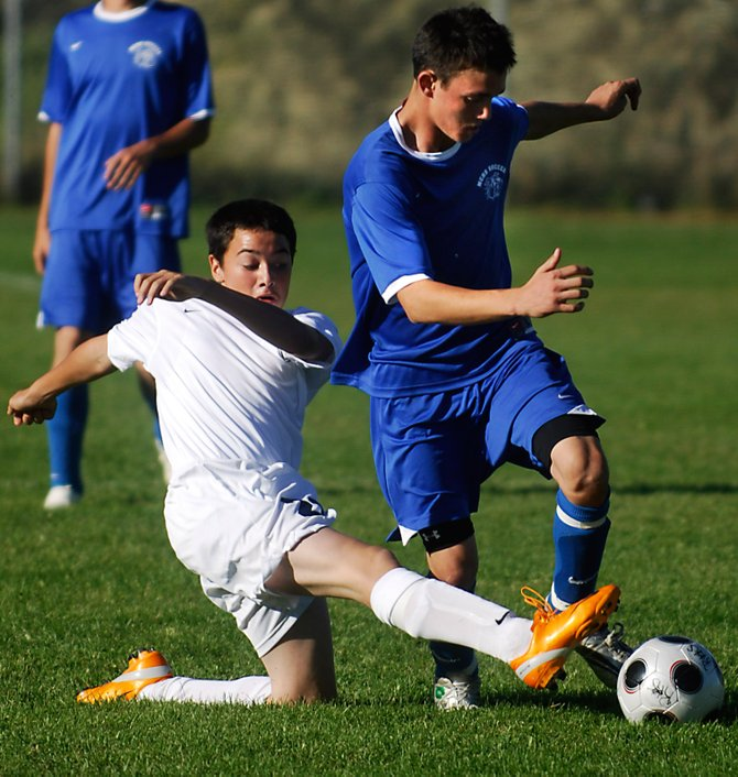 Moffat County High School's Dustin Carlson battles with Fernando Carreon for possession of the ball during the Bulldogs' 3-1 loss to host Rifle High School on Thursday afternoon.