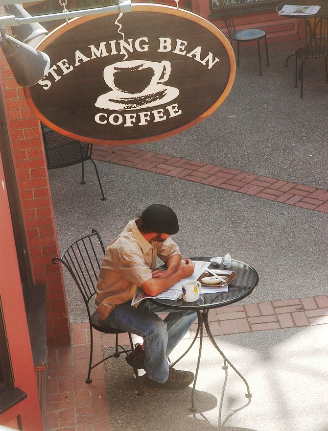 Steamboat Springs resident Jeff Coates has a bagel and coffee  Thursday afternoon outside Steaming Bean Coffee. Todd Moore, the owner of the Steaming Bean, has decided to put the coffee shop up for sale.