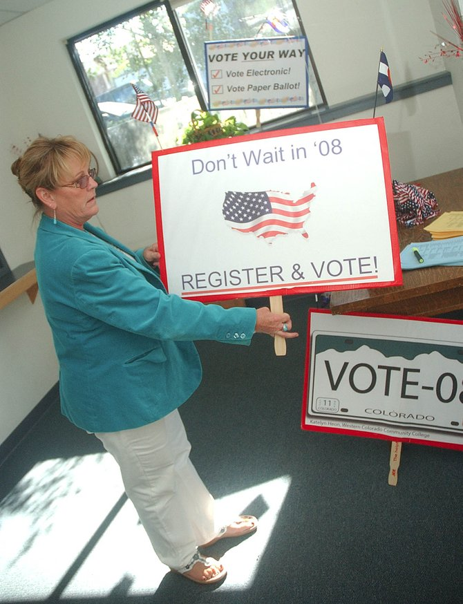 On Thursday, Routt County Clerk and Recorder Kay Weinland holds one of the bipartisan election signs that have been made available to raise awareness of registering and voting early in 2008. The last day to register to vote is Oct. 6.
