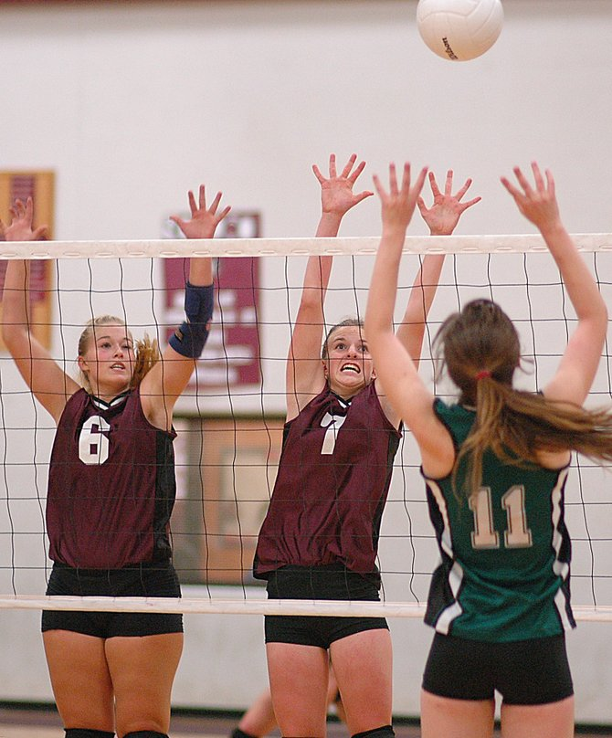 Soroco senior Katrina Maes, left, and freshman Lindsay Miles get high to try to block a Plateau Valley attack Friday night. Thanks to a scrappy defense and consistent play, the Rams won their first match of the season, beating the Cowboys in four games.
