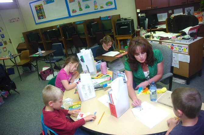 Rock Creek Academy teacher Becky Ingle works with students at the charter school in McCoy on Friday. Seven students are enrolled in the school's first year.