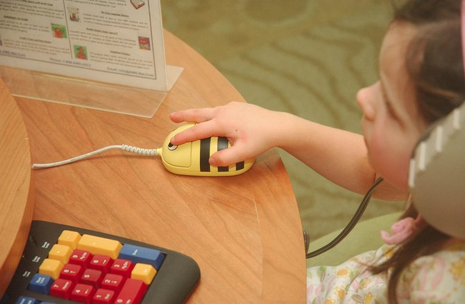 Three-year-old Eileen Cashen plays a reading computer game using a mouse designed for children at the Bud Werner Memorial Library on Thursday.