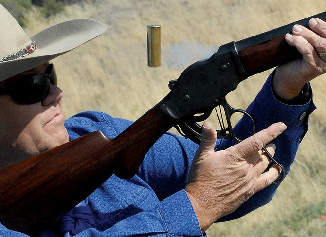 Jon Ossen fires his single-action rifle at four round-metal targets. The single-action rifle was one of three different guns used during a local gun club's event.