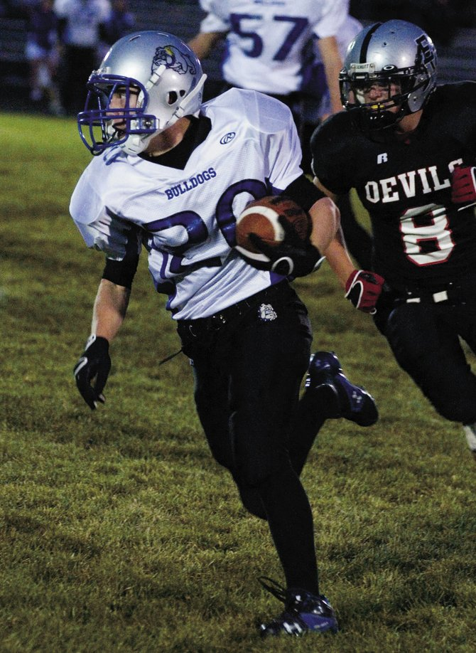 Moffat County's Jason Kettle runs past Eagle Valley's Ryan Green during Friday's game in Gypsum. The Devils were too much for the Bulldogs, with Moffat County losing, 44-21.