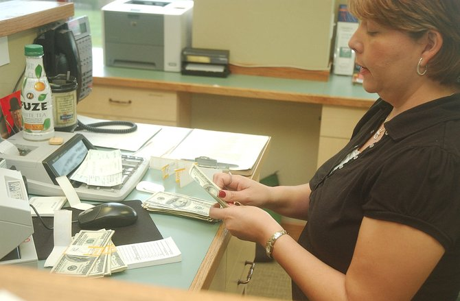 Mountain Valley Bank Teller Claudia Milano counts $100 bills at the bank Thursday.