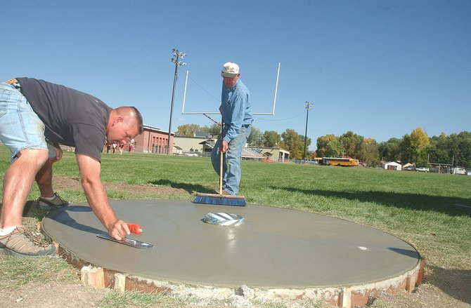 Hayden American Legion Post 89 members Larry Pederson, left, and Ron Nereson work Tuesday on the foundation for a new flagpole being placed at the Hayden High School football field.
