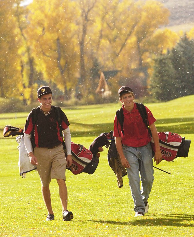 Steamboat Springs High School golfers Scott Ptach, right, and Kaelen Gunderson walk down the fairway during an afternoon rain shower Thursday at Steamboat Golf Club.