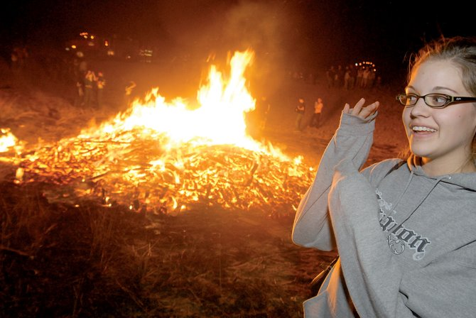 Sarah Bolton shields herself from the intense heat Thursday at Moffat County High School's annual bonfire. Bolton, a senior, was among 200 to 300 people who gathered behind the high school to watch the large pile of wood burn. See page 11 for more bonfire coverage.