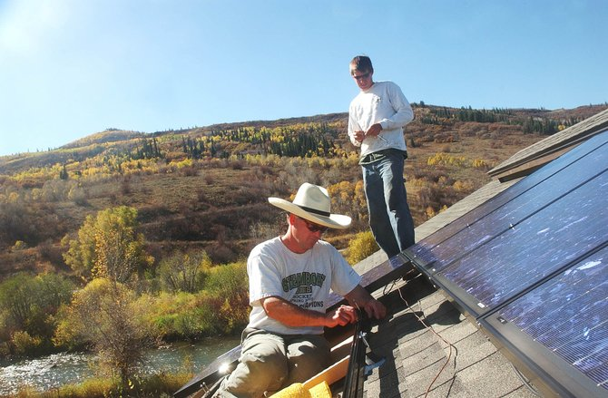Tim McCarthy, front, and Kevin Schneider with Emerald Mountain Energy install a 3.5 kilowatt photovoltaic system Wednesday afternoon on the roof of the Trillium House under construction at the Yampa River Botanic Park.