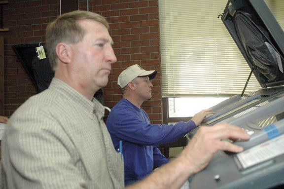 John Ponikvar, with the Moffat County Republican Central Committee, and Walker Criswell, with Moffat County Democrats, enter pretend ballots into the county's electronic voting machines Thursday. They participated in the local public test of electronic voting equipment and found the machines counted ballots accurately in all cases.