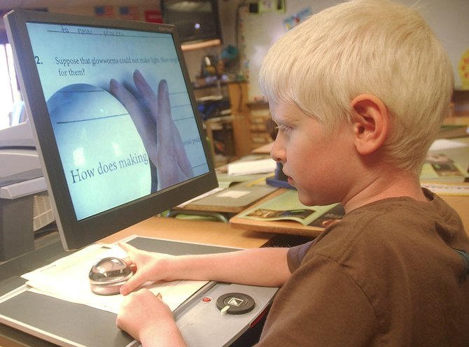 Third-grader Miles Buchan uses a magnifier to assist him with completing an assignment at Strawberry Park Elementary School.  The magnifier is one of the adaptive devices used for children with disabilities at the school.