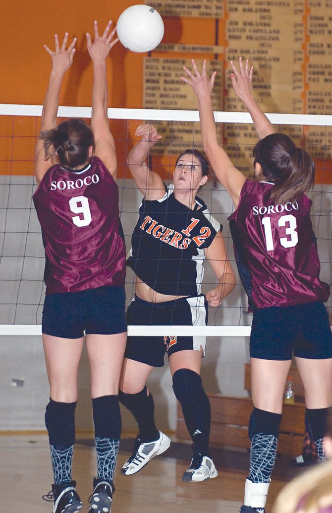 Hayden's Holli Salazar hits through the block of Soroco sisters Sarajane and Ceanna Rossi during Friday night's showdown in Hayden. The Tigers won the match in three games.