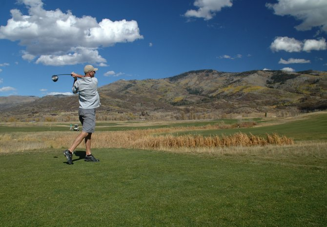 Mount Werner looms in the background as Ivelin Dimitrou, of Steamboat Springs, tees off at Haymaker Golf Course on Thursday afternoon. Haymaker and the rest of Steamboat's golf courses will close in the next month, but all say there is plenty of time to squeeze in a few good rounds.