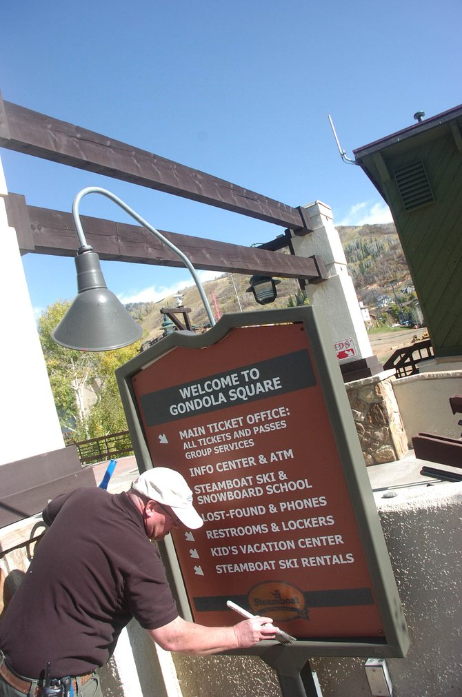 Steamboat Ski and Resort Corp. employee Brian Crowe touches up a sign Tuesday at the entrance to Gondola Square.