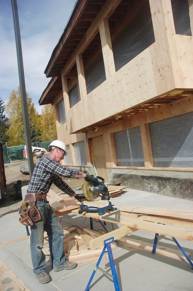Zach Williams, with Peak Construction, cuts a board Thursday at Bud Werner Memorial Library, which is utilizing lumber certified by the Forest Stewardship Council for remodeling.