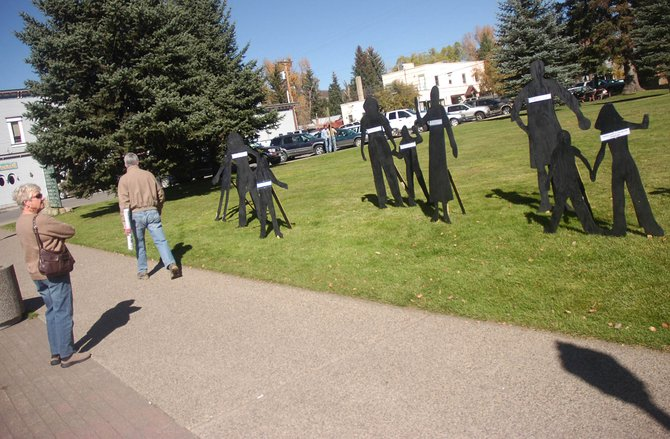 Jane Ramage, of Medford, Ore., looks Friday afternoon at a domestic abuse awareness display set up in front of the Routt County Courthouse.