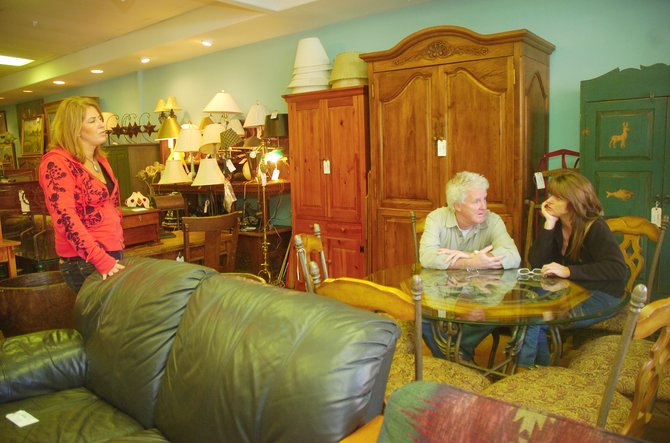 Annie's Home Consignments owner Annie Tisch talks to customers Jack Doyle and Jenny Gentry on Thursday at the store.