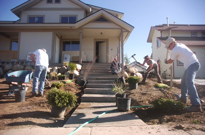 Cam Boyd and Colleen de Jong, with Prudential Steamboat Realty, swing picks Friday while working on landscaping in front of a Routt County Habitat for Humanity house nearing completion in West End Village. Also pictured is Jack Carter.