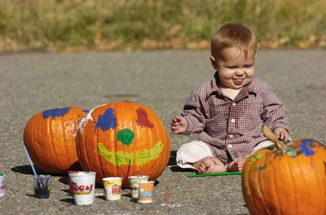 Eight-month-old Daniel McLaughlin sits on the ground after finishing painting pumpkins Saturday during the 18th annual Pumpkin Festival at the Brent Romick Rodeo Arena. Daniel was at the event with his dad, Don McLaughlin.