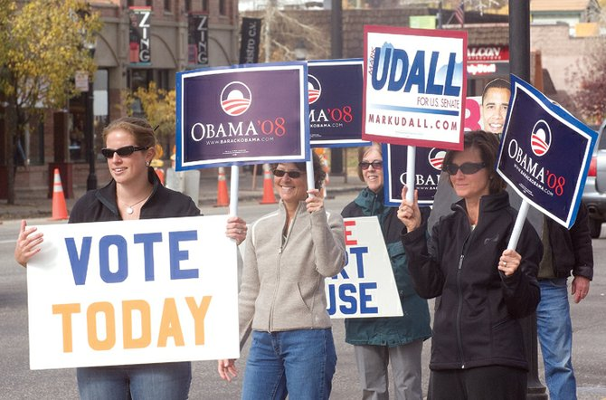 Volunteers, left to right, Torey Wodnik, Audrey Kruse, Diane Carter and Beth Wendler seem to be backed by presidential candidate Barack Obama on Monday while urging passing motorists to go vote Monday on the first day of early voting in Steamboat Springs.  The volunteers, who were all with the Obama Campaign, held up signs, including one depicting Obama himself, for Democratic candidates and a few that simply reminded people they could go vote.