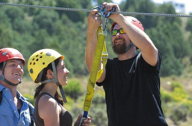Zip Adventures guide Jason Leach secures a safety line just before 13-year-old Sylvie Sapidin steps over a canyon wall on a journey that will carry her more than 100 feet above Alkali Creek near Wolcott. Zip Adventures is celebrating its first full year of operation.