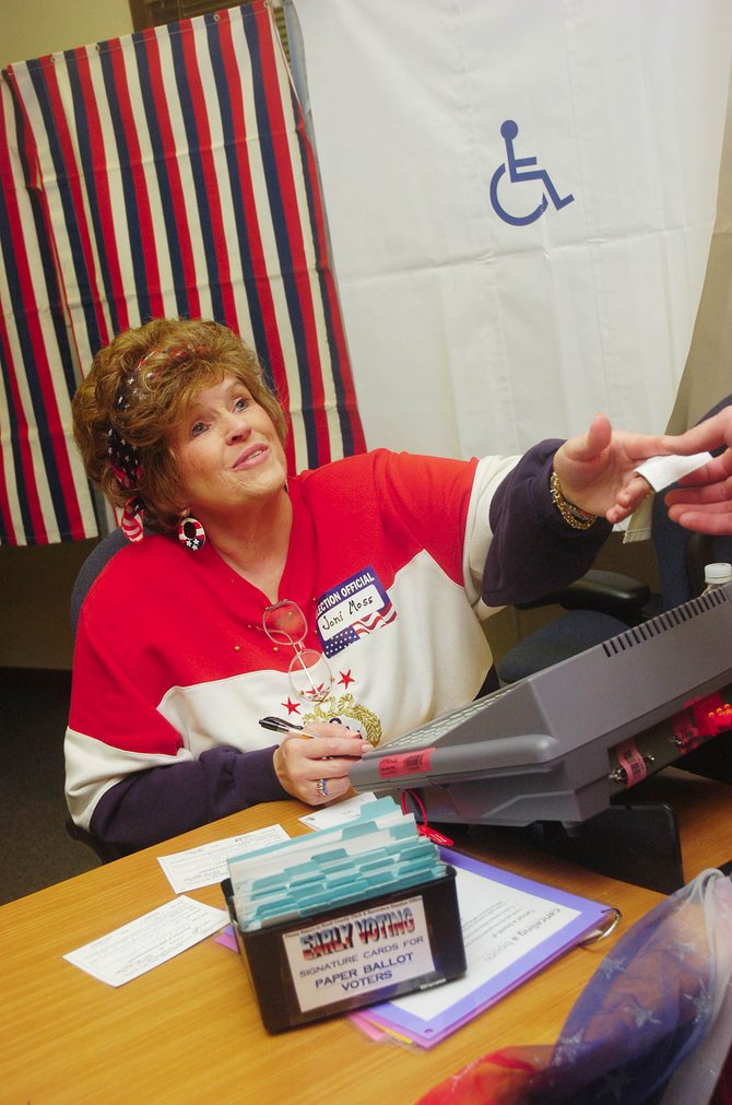 Election judge Joni Moss hands a voter an access code for an electronic voting machine Friday at the Routt County Courthouse.