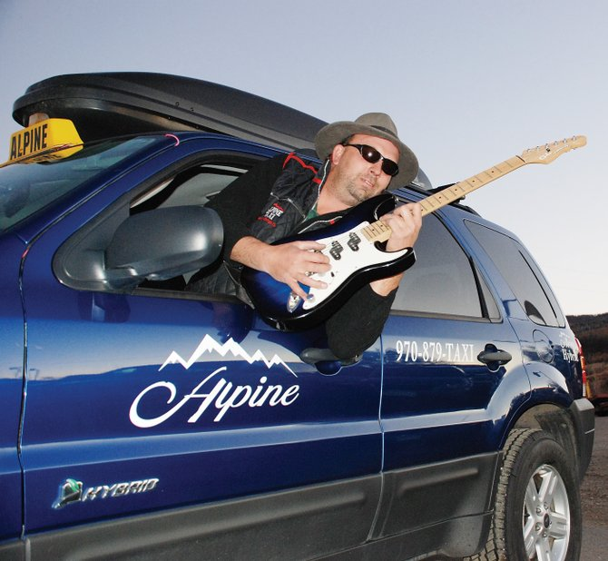 Cabbie Rich Van De Carr plays a blue guitar in a blue car. The cab runs on hybrid energy, but Van De Carr runs on blues power.