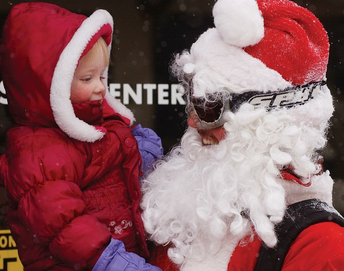 Katherine Knapp, of Steamboat Springs, visits with John Evans, who was skiing dressed like Santa Claus last Christmas at the Steamboat Ski Area. Some worry the economy will limit tourist occupancy this year, but others predict the difference won't be noticeable.
