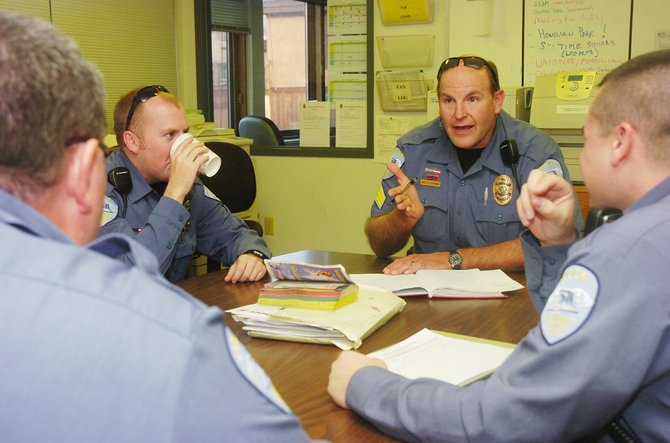 Steamboat Springs Police Sgt. Dale Coyner briefs officers, clockwise from right, Tom Munden, John McCartin and Bill Stucker on Friday at the police department. The economy could have effects on increased criminal activity, Sheriff Gary Wall said.