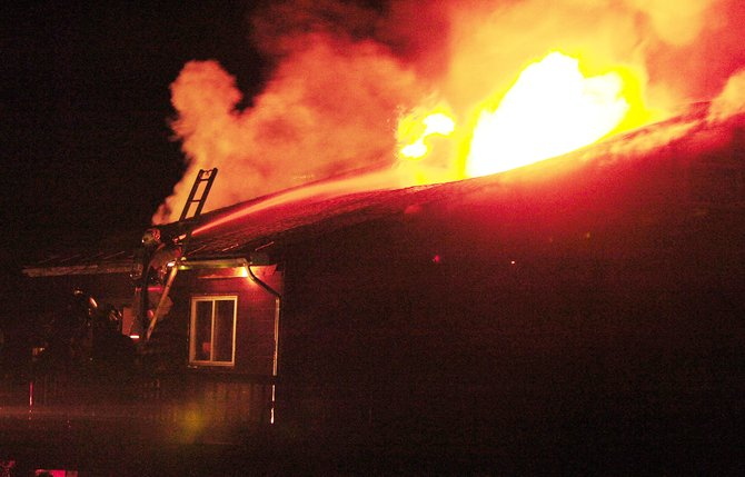 Firefighters try to put out flames coming from the roof of a house that caught on fire Saturday evening in Stagecoach.