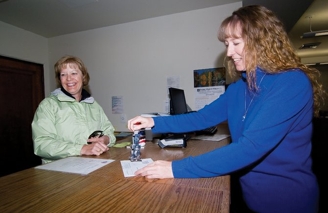 Tina Fry, county recording supervisor, stamps a mail-in ballot that was dropped off Monday by Susan Hoffner at the Routt County Courthouse. With Election Day just one week away, Routt County residents are taking advantage of early voting and the mail to cast their votes.