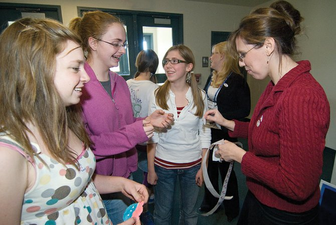 "Ninth graders Sara Pugh, Aimee Lotz and Melodie Houston get ""I voted Stickers"" from history and government teacher Melissa Weisberg, who dressed like Sarah Palin, after voting at Christian Heritage School's mock election Tuesday afternoon."