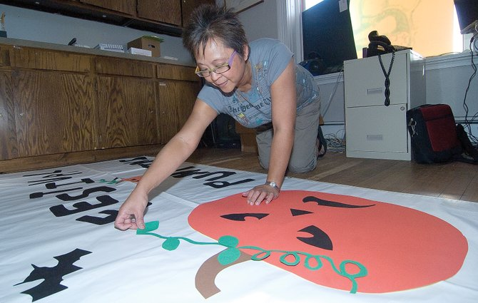 Pamela Peretz, special events coordinator for the Steamboat Springs Arts Council, makes a banner for the Festival O' Pumpkins. The festival is scheduled to take place on the courthouse lawn starting at 5:30 p.m. Friday.