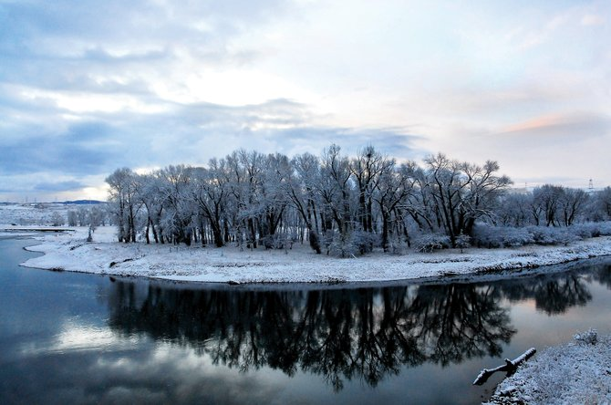 Trees are reflected in the Yampa River early Wednesday morning west of Highway 13. The first snow hit Northwest Colorado leaving several inches on the ground with snow continuing throughout the day.