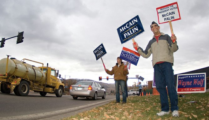 Keenan Starbuck (with the Ronald Reagan mask) and Mike Makens hold signs showing their support for John McCain and Bob Schaffer on U.S. Highway 40 on Tuesday afternoon. The long elections process came to an end Tuesday when the final votes were cast. 