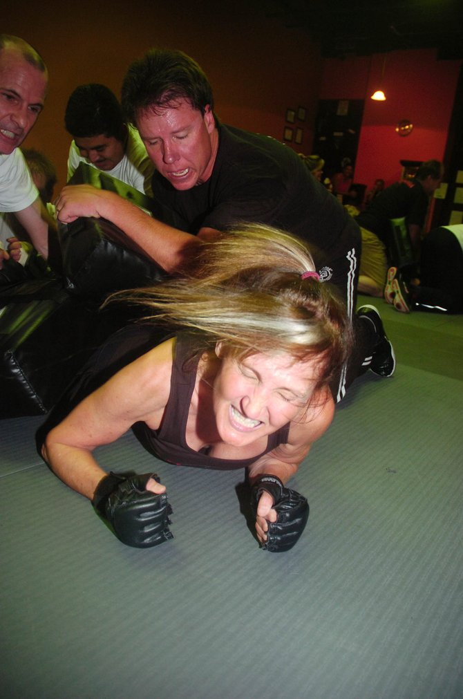 Krav maga student Kim Tilley tries to get loose during the dog pile exercise, where multiple people try to keep the person on the bottom from escaping.