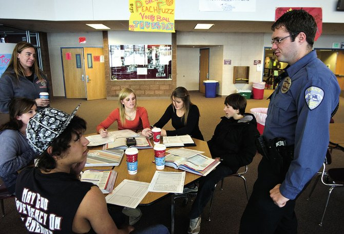 Steamboat Springs Police Officer Josh Carrell, right, talks with high school students in the commons area last year. Carrell is the high school's resource officer. The city and school district are discussing the possibilty of sharing the costs of the position, which usually has been paid for in full by the city.
