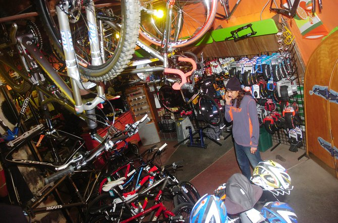 Orange Peel Bicycle Service employee Essam Welch talks on the phone Tuesday at the shop. Despite the cold temperatures and snow, Welch said there still are opportunities to mountain bike.