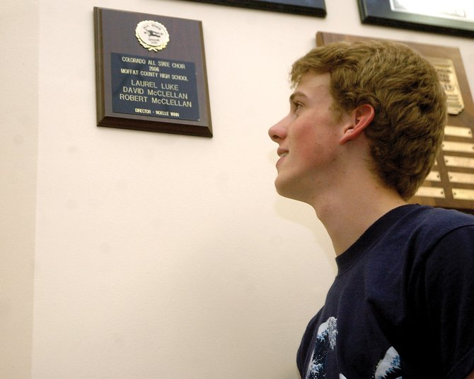 Daniel McClellan, 17, a Moffat County High School junior, looks at a plaque in the MCHS choir room listing the names of his older brothers, David and Robert, who qualified in both sets of auditions for Colorado All State Choir in 2006. Last month, McClellan earned 91 points out of 100 in the first round of auditions for All State Choir, making him the first MCHS student in two years to qualify for the event.
