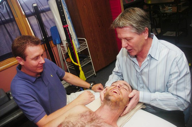 Physical therapist Greg Johnson, left, watches as Johnson & Johnson Physical Therapy co-owner Gregg Johnson mobilizes the upper neck of patient Jeff Gibson.