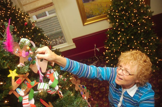Suzy Holloran, an art teacher with Horizons Specialized Services, decorates a Christmas tree Thursday at the Tread of Pioneers Museum. Horizons is one of several organizations decorating a tree for the Festival of Trees, an annual holiday fundraiser for the museum.