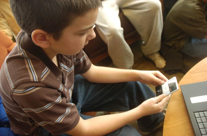 "Josh Winge, 11, tries out a microphone attachment for his iPod during Friday's ""23 Things to do with Your iPod"" workshop at Bud Werner Memorial Library."